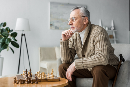 thoughtful retired man in glasses thinking while sitting near chess board at home 版權商用圖片