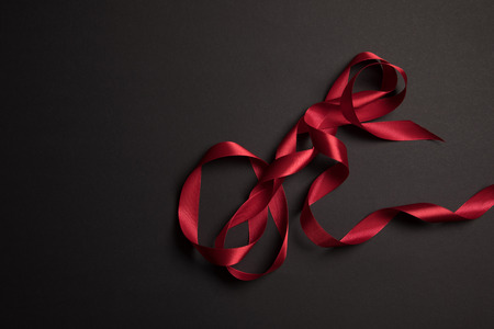 top view of red satin ribbon on black background with copy space