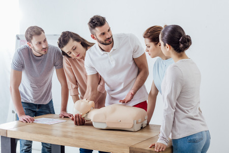 group of people with cpr dummy during first aid training class
