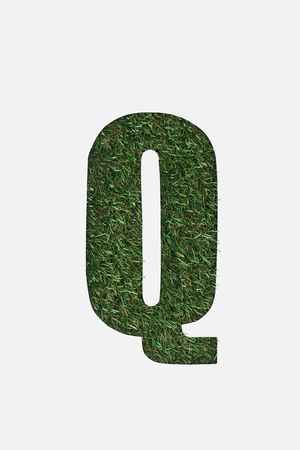 top view of cut out Q letter on green grass background isolated on white