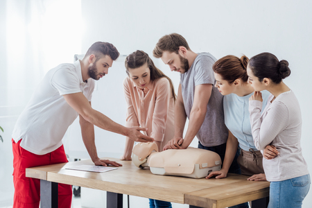 group of people with handsome instructor performing cpr on dummy during first aid training