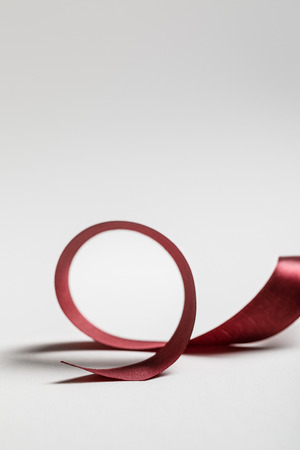 satin curved burgundy ribbon on grey background