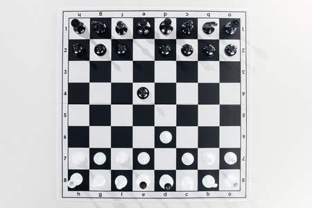 top view of black and white chessboard with figures on white background Stok Fotoğraf