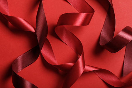 close up of silk burgundy and red ribbons on red background
