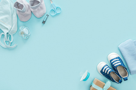 top view of scissors, pacifiers, gift, sneakers, bonnet, booties, hat on blue background