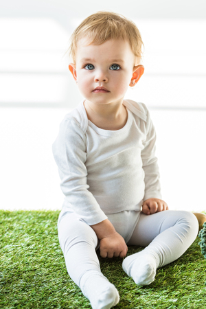 cute child with blonde hair sitting on green grass and looking away on white