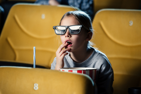 cute attentive child in 3d glasses eating popcorn in cinema