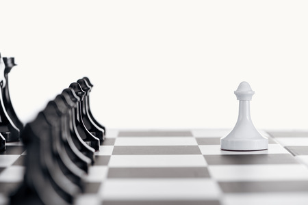 selective focus of chessboard with black chess pieces and white pawn in front isolated on white