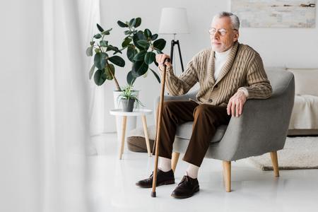 homme retraité à lunettes assis dans un fauteuil avec canne Banque d'images