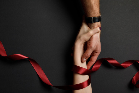 cropped view of man and woman in red satin ribbon holding hands on black background