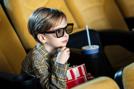 Adorable niño con gafas 3d sosteniendo un vaso de papel con palomitas de maíz Foto de archivo