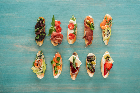 top view of italian bruschetta with salmon, dried tomatoes, prosciutto and herbs on wooden table