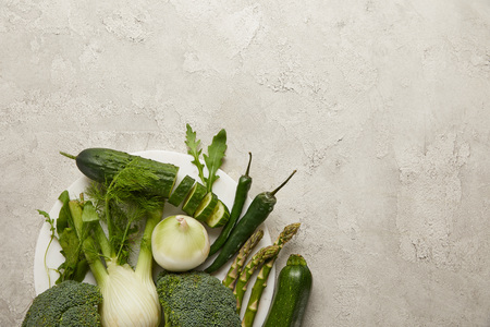 Top view of fresh vegetables on grey textured surface