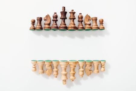 top view of rows made of brown and beige wooden chess figures on white background with copy space Stok Fotoğraf