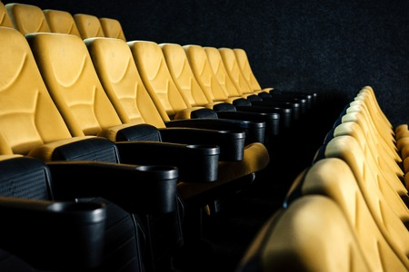 selective focus of comfortable orange cinema seats with cup holders