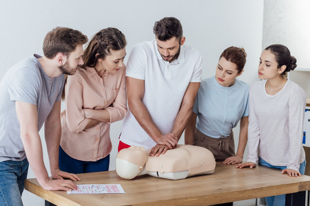 group of people looking at man performing cpr on dummy during first aid training Stock Photo