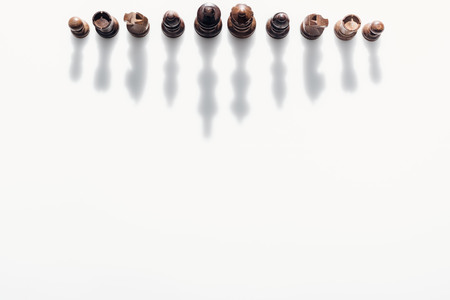 top view of brown chess figures with shadows on white background