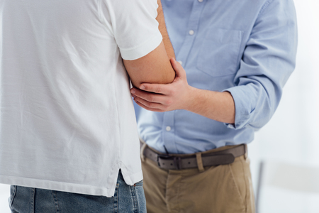 cropped view of men consoling another man during therapy meeting