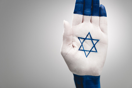 cropped view of female hand with jewish star of david on grey