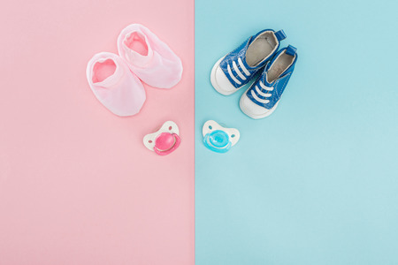 top view of pacifiers, booties, sneakers on pink and blue background with copy space Stockfoto