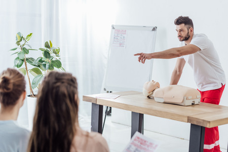 handsome instructor with cpr dummy pointing with finger during first aid training class