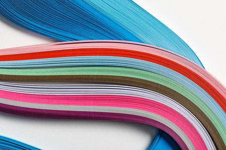 close up of wavy multicolored rainbow paper lines on grey background