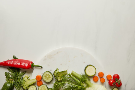 Top view of whole and cut vegetables on white surface Stok Fotoğraf