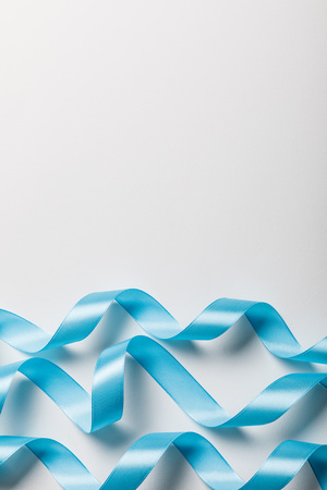top view of blue wavy satin ribbons on grey background with copy space Stock Photo