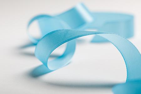 close up of wavy blue satin ribbon on grey background