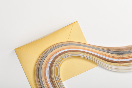 yellow envelope with multicolored paper lines on grey background