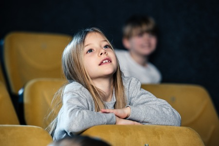 selective focus of cute attentive child watching movie in cinema