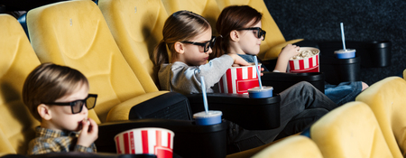 panoramic shot of children watching movie in 3d glasses and eating popcorn in cinema