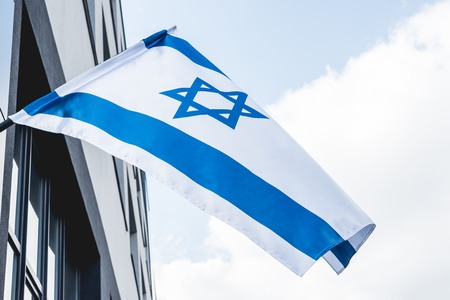 low angle view of national israel flag with star of david near building against blue sky Stock Photo