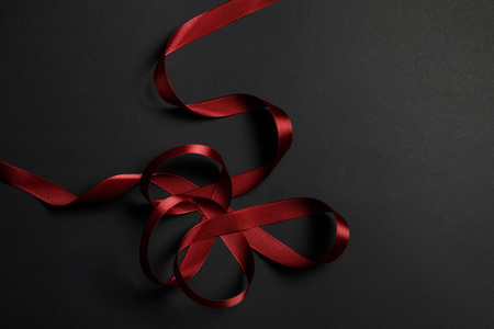 top view of red satin wavy ribbon on black background with copy space Stock Photo