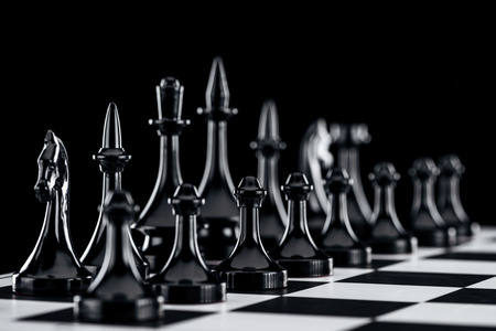 selective focus of chessboard with black chess figures isolated on black Imagens