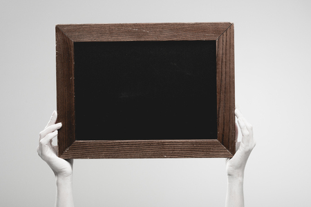 cropped view of female hands painted in white holding empty chalkboard isolated on grey