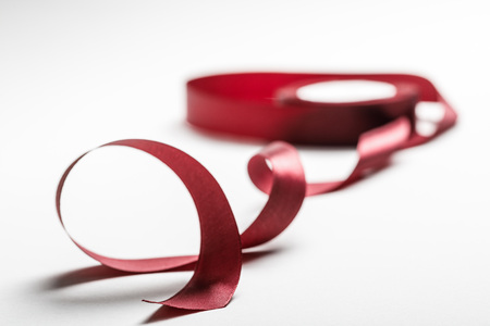 selective focus of satin wavy burgundy ribbon with spool on grey background Stock Photo