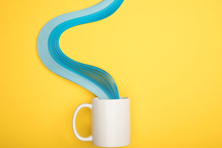 top view of white cup and blue curved lines on yellow background