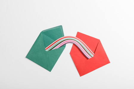top view of green and red envelopes with multicolored rainbow on grey background