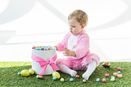 cute baby in pink fluffy costume sitting on green grass near gift box with pink bow and colorful Easter eggs isolated on white Banco de Imagens
