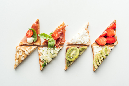 top view of toasts with strawberries, avocado, kiwi and prosciutto isolated on white 写真素材