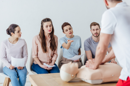 back view of instructor performing cpr on dummy during first aid training with group of people Archivio Fotografico