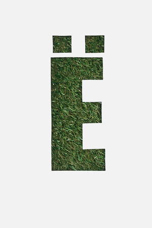 top view of cut out cyrillic letter with natural grass on background isolated on white