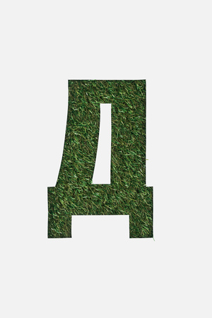 top view of cyrillic letter with green grass on background isolated on white