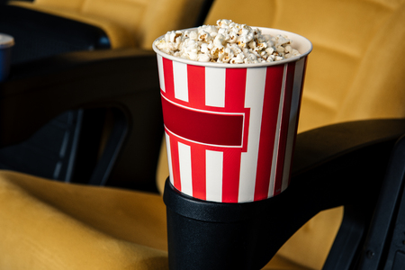 selective focus of cinema seat with stripped paper cup of popcorn in cup holder Stok Fotoğraf