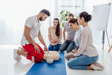 instructor gesturing during first aid training with group of people Imagens