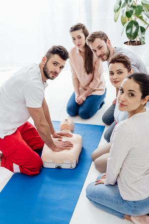 groupe de personnes avec instructeur regardant la caméra pendant la formation aux premiers secours