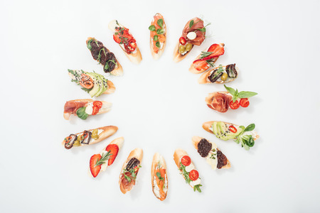 top view of round frame made of traditional italian bruschetta with salmon, prosciutto, herbs and various fruits with vegetables