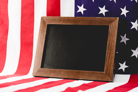 empty black board near american flag with stars and stripes Stock Photo