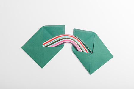 top view of green envelopes with multicolored rainbow on grey background